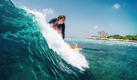 Happy lady surfer rides the tropical wave at sunny day Banco de Imagens