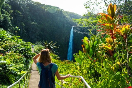 Woman hiker stands on the path and watches waterfall in the tropical forest