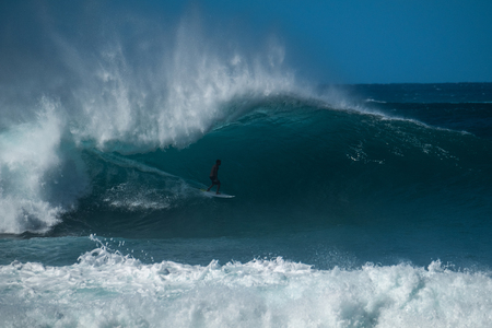 Extreme surfer rides gigantic ocean wave of the Banzai Pipeline surf spot. The North Shore of Oahu, Hawaii
