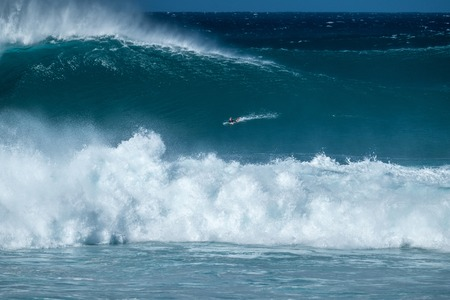 Extreme surfer paddles and going to ride the gigantic ocean wave of the Banzai Pipeline surf spot. The North Shore of Oahu, Hawaii
