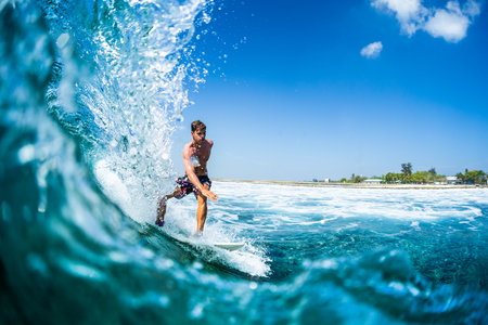 Surfer rides barreling tropical ocean wave Stock Photo