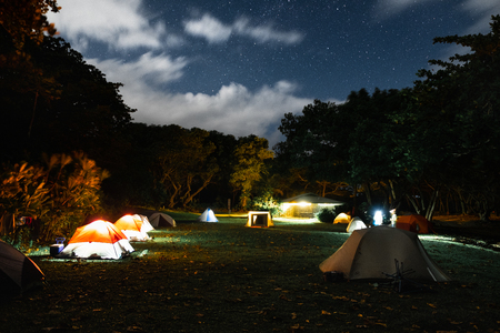 Green lawn with hiking tents set under the stars in the camping of Waianapanapa State Park. Maui, Hawaii