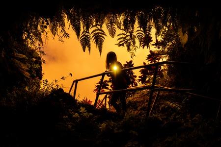 Une femme se tient près de l'entrée du tube de lave entourée d'une végétation tropicale luxuriante et clignote avec la lumière d'une torche directement dans l'appareil photo. Maui, Hawaï
