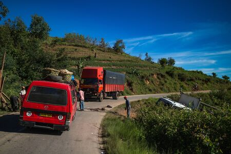 FIANARANTSOA  MADAGASCAR - 24 DECEMBER 2013: Random cars stopped on the mountain road and men help to get cargo truck out from the ditch