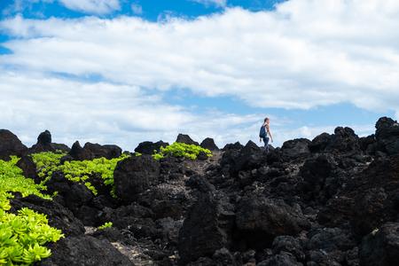 Woman hiker walks on the sharp volcanic land. Maui, Hawaii