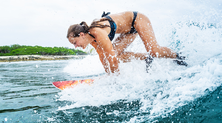 Happy young woman learns surfing in the tropics