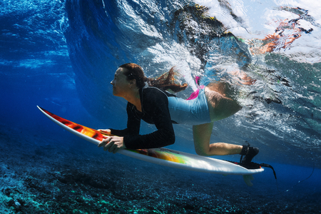 Underwater shot of the young woman surfer diving under the wave with her surfboard Stockfoto