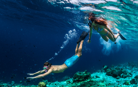 Young couple snorkeling and do skin diving on the coral reef edge in tropical waters of the Maldives