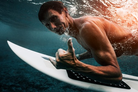 Muscular adult surfer dives under the wave with surfboard and shows the Shaka sign Banque d'images