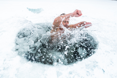 Young man haves recreational winter swim in the lake
