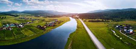 Aerial panorama of the river of Belaya with the villages on its green coasts, asphalt road along the river and Ural Mountains on the horizon