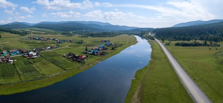 Aerial panorama of the river of Belaya with the village on its green coast, asphalt road along the river and Ural Mountains on the horizon Stock Photo
