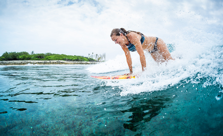 Happy young woman learns surfing in the tropics Фото со стока - 123362803