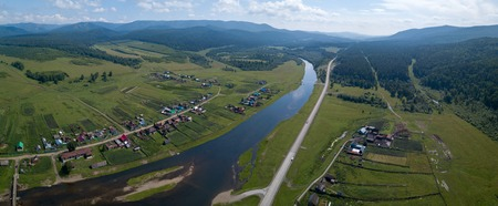 Aerial panorama of the river of Belaya with its green coasts with villages and Ural Mountains on the horizon