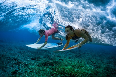 Two surfers dive under the wave with surfboards