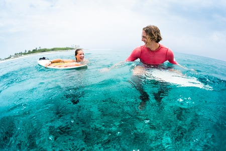 Two young and happy surfers have fun in the ocean - man sits on the board and woman swims and look at the man