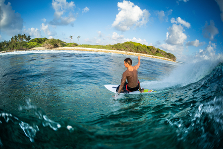 Surfer rides the ocean wave at sunset. Honkeys surf spot in the Maldives 版權商用圖片