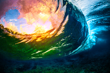 Underwater view of the crystal clear ocean wave barreling over the coral reef with clouds and sunset sky visible through the water Stock Photo