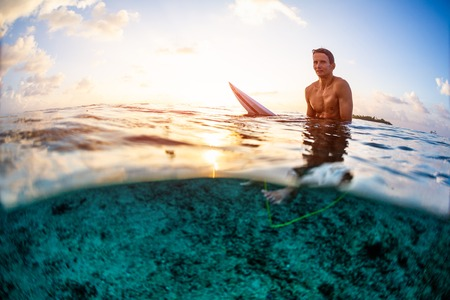 Surfer sits on the surfboard and looks at the camera at sunset. Splitted view with underwater view