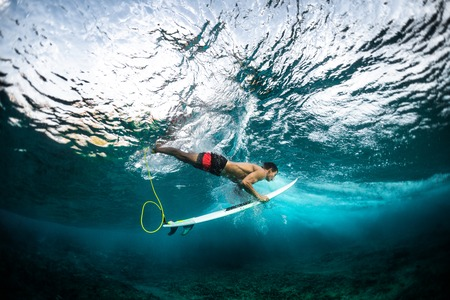 Surfer dives under the wave with his surfboard