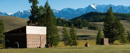 Young couple, man and woman relax after sauna on the green summer meadow with snow capped mountains on the background. Altai Republic, Russia