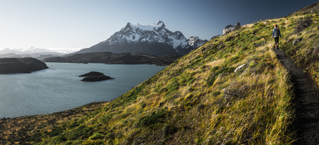Panorama with the woman hiker walking on the trail in the Torres del Paine National Park. Chile.
