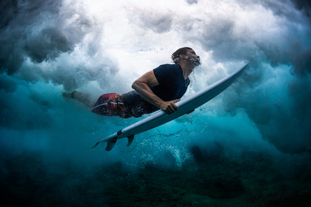 Young male surfer dives under the broken wave with his surfboard