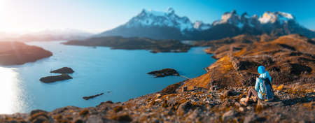 Woman hiker sits on the rock and enjoys spectacular view of the snow capped mountains and the blue lake in the Torres del Paine National Park in Chile. Tilt shift effect applied