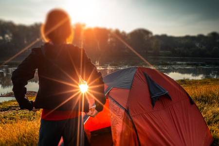 Young woman hiker stands near the tent and enjoys sunrise over the river. Tilt shift effect applied