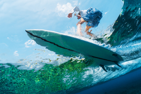 Underwater view of the surfer riding the crystal clear ocean wave