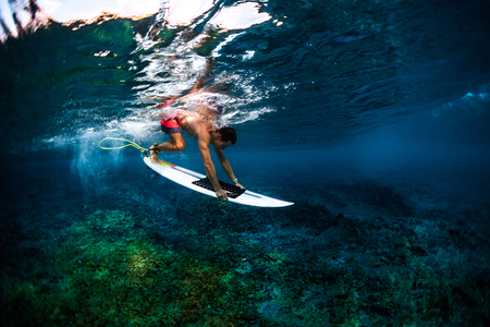 Surfer dives under the wave with his surfboard over the sharp reef with uneven surface