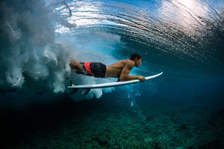 Surfer dives under the breaking wave in the tropics Imagens
