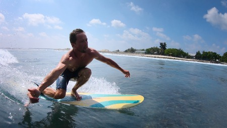 Young man rides the tropical ocean wave on fun board and shows the Shaka sign 版權商用圖片