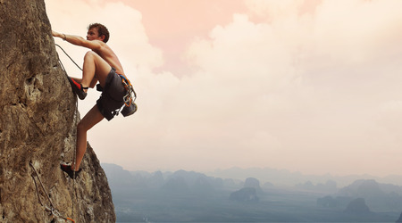 Jonge man klimmen op een kalkstenen muur met brede vallei op de achtergrond