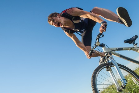 Young man screams while falling from the bicycle in the green field