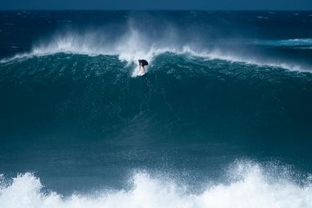 Un surfeur chevauche une vague géante sur le célèbre spot de surf de Banzai Pipeline situé sur la côte nord d'Oahu à Hawaï