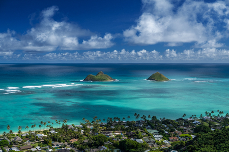 Hawaiian tropical coast with buildings among the palm trees and two islands in the Pacific Ocean Stock fotó