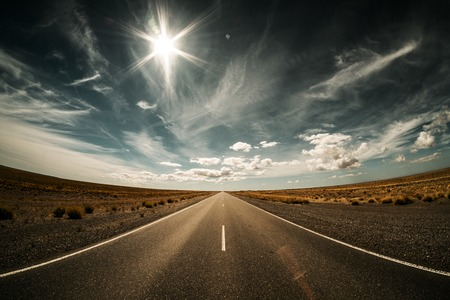 Empty asphalt road in Argentinean pampa with dry grass on its sides and bright sun in the sky