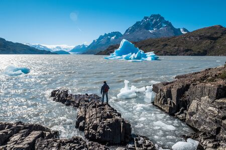 Young man stands on the rocky coast of the Grey Lake and enjoys the blue iceberg view. Torres del Paine National Park, Chile
