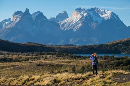 Woman hiker takes picture of the Cordillera Paine mountains in the Torres del Paine National Park in Chile Stock fotó