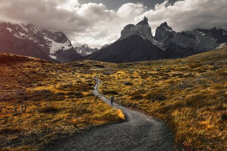 Woman hiker walks on the trail in Torres del Paine National Park, Chilean Patagonia. Stock fotó