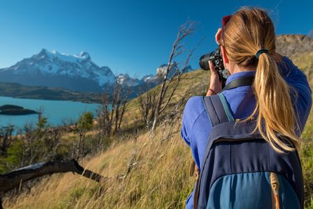 Woman photographer takes photo of the mountains in Torres del Paine National Park in Chile