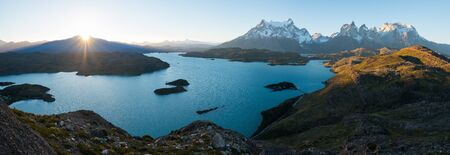 Panorama of Torres del Paine National Park with snow capped mountains (Cordillera Paine) and blue lake of Pehoe as seen from the Mirador Condor during sunset. Chile