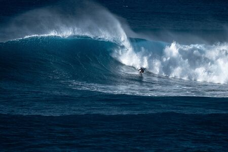 Surfer reitet Riesenwelle am berühmten Surfspot Waimea Bay an der Nordküste von Oahu auf Hawaii Standard-Bild