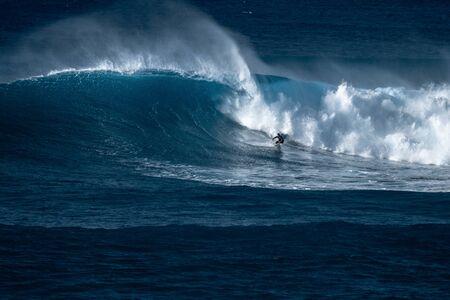 Un surfeur chevauche une vague géante sur le célèbre spot de surf de Waimea Bay situé sur la côte nord d'Oahu à Hawaï Banque d'images