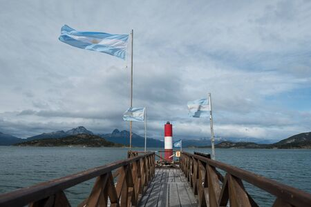 National Argentinean flags and wooden pier near the southernmost Agrentinean post office