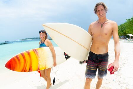 Two happy surfers, caucasian man and woman smile and walk with their surf boards along the sandy beach after surf session. Both look at the camera.