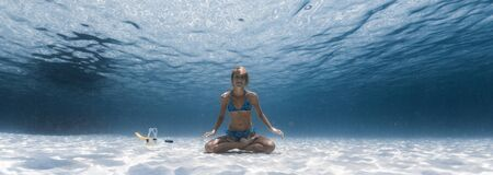Slim yogi lady sits on the sandy sea bottom in the relaxed Lotus pose, smiles and looks at the camera