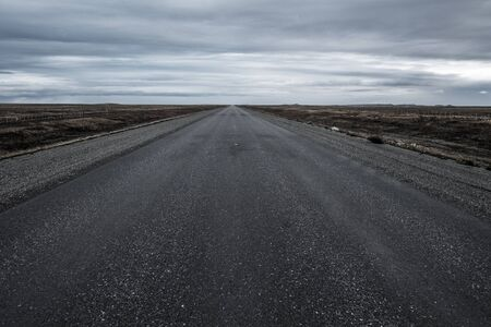Asphalt empty road and rainy clouds in the Chilean part of the Tierra del Fuego.