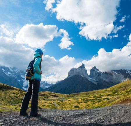 Woman hiker stands on the trail and enjoys the view of the mountains in Torres del Paine National Park, Chilean Patagonia. Stock fotó